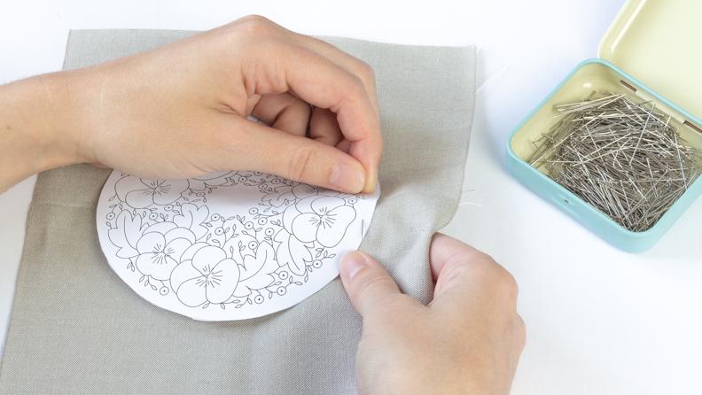 center le motif sur le tissu et le maintenir avec une épingle